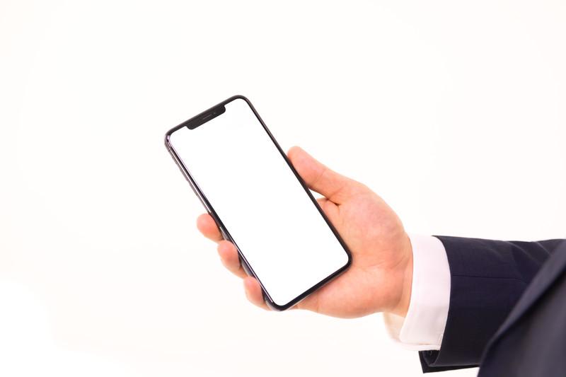 スマートフォンを手に持っている