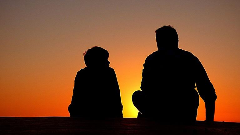 夕日の中で父親と息子が語り合っている