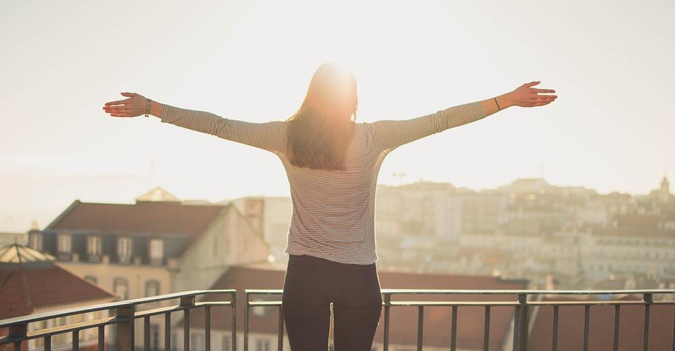 両手を広げて太陽の光を浴びる女性