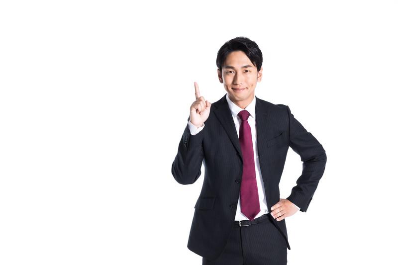 人差し指を立てているスーツの男性
