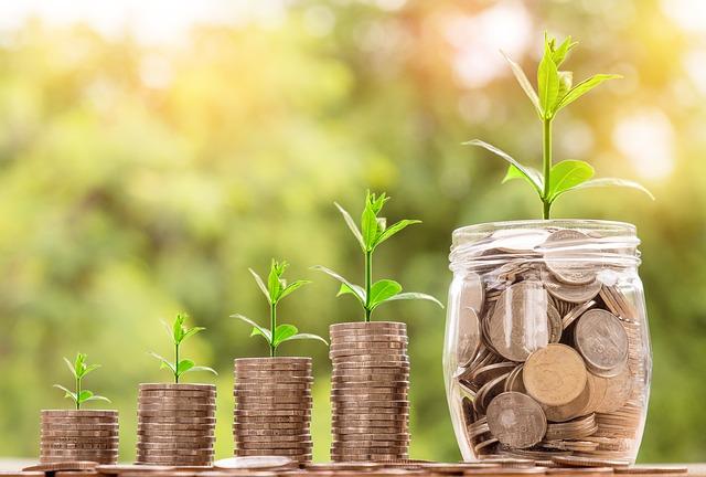 小銭が階段のように増えていて、一番上の小銭から植物の芽が生えている