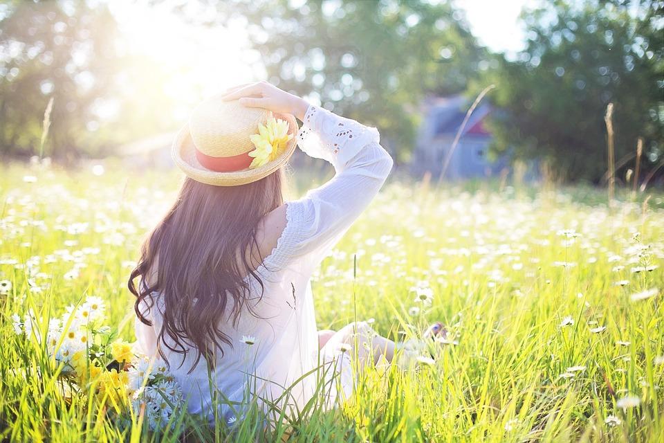 太陽の光を浴び、帽子を手で押さえている女性の後姿。