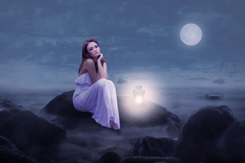 外で月の光にあたって岩の上に座っているいる女性