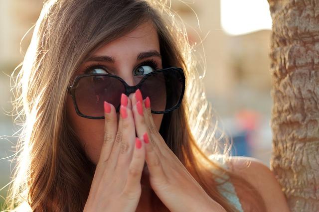 サングラスをかけた女性が、びっくりして両手で口元を押さえている