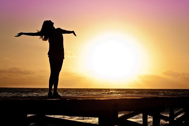 海の横で夕日に照らされ、幸せそうに両手をせいいっぱひろげる女性のシルエット