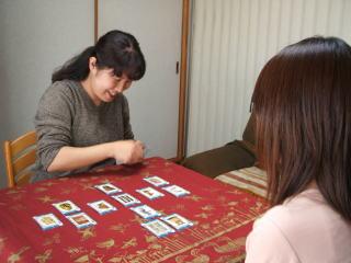 カードを並べて笑顔で占いをする長田志帆