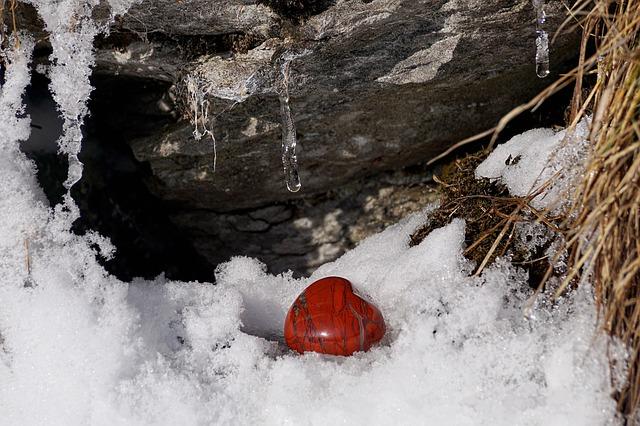 雪の上に赤いハートの形をした天然石がある