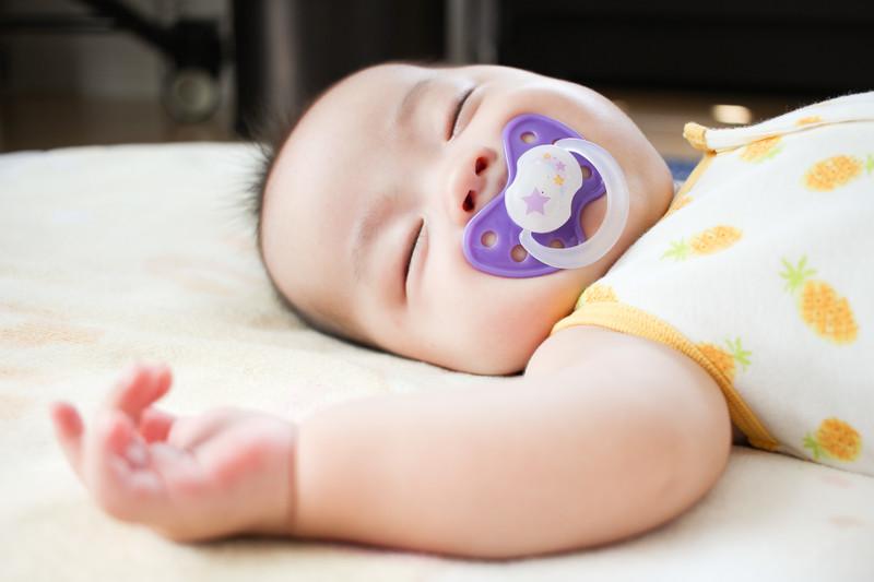 おしゃぶりをつけてすこやかに眠る赤ちゃん