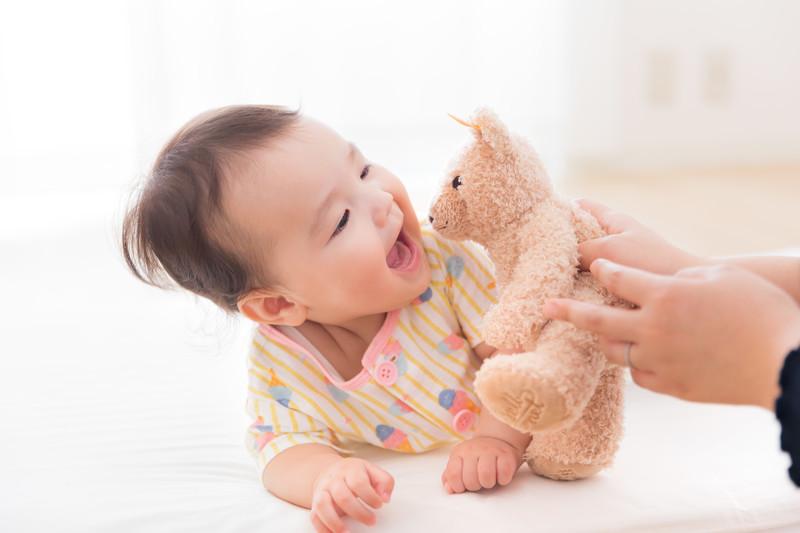 赤ちゃんがクマのぬいぐるみを見て笑っている