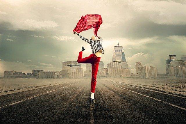 両手片足を上げ幸せを表現する女性