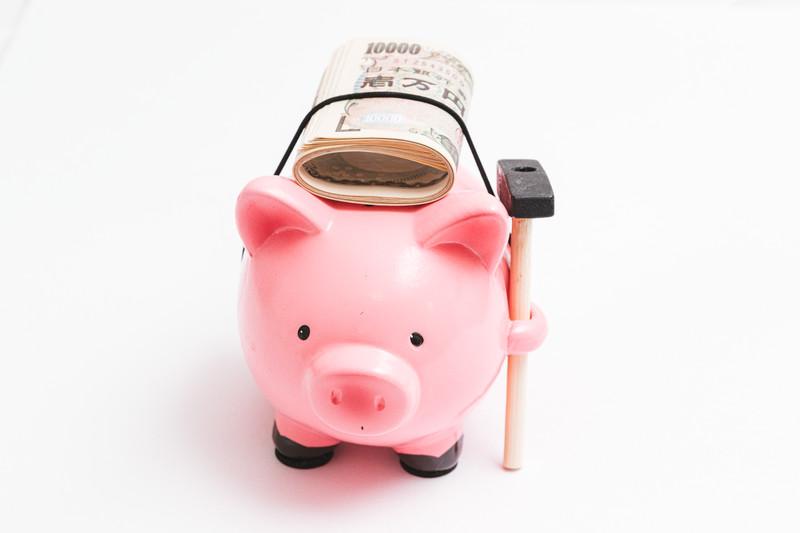 豚の貯金箱の上に札束が乗っている