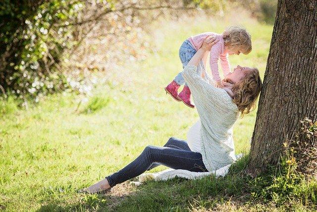 木陰に座ったお母さんが赤ちゃんを高く持ち上げて微笑んでいる