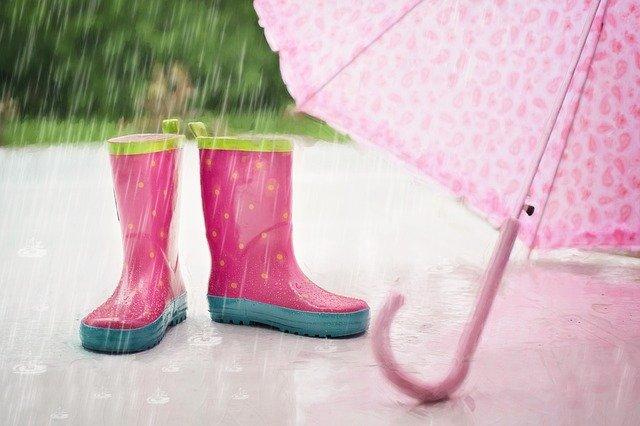 雨が降っている中に置かれた子供用の長靴と傘