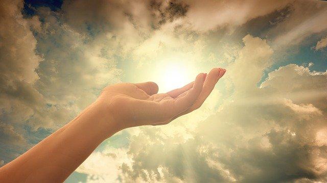 片手を空にかざし手のひらに太陽の光が乗っている