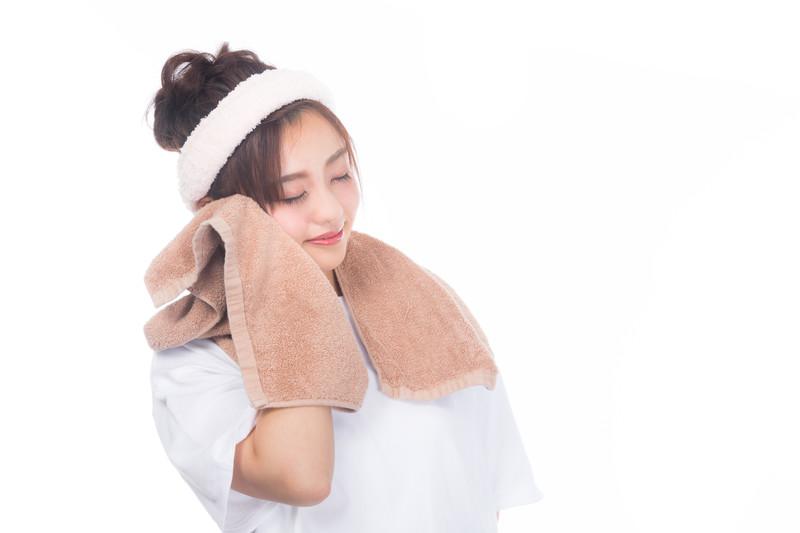 タオルで頬を覆う女性