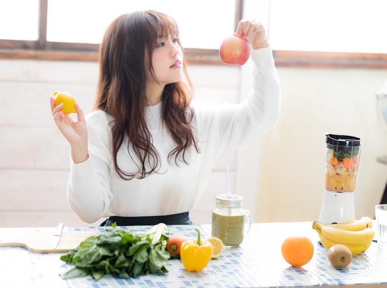 果物(リンゴ・レモン)を選ぶ若い女性