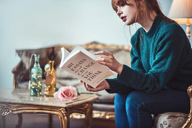 ソファでくつろぎ本を読む女性の写真