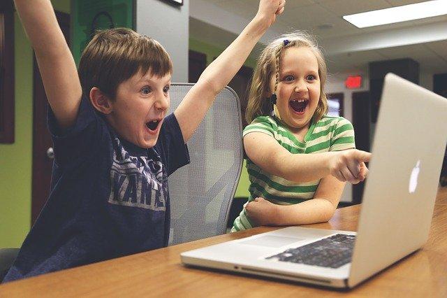 子どもがパソコンを見てバンザイをしている写真