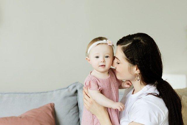 ママが小さい女の子のほっぺたにキスしている写真