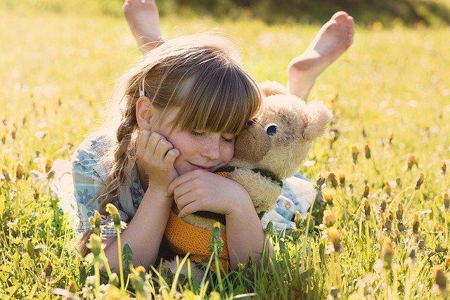 子どもが芝生の上でぬいぐるみを抱き微笑んでいる写真