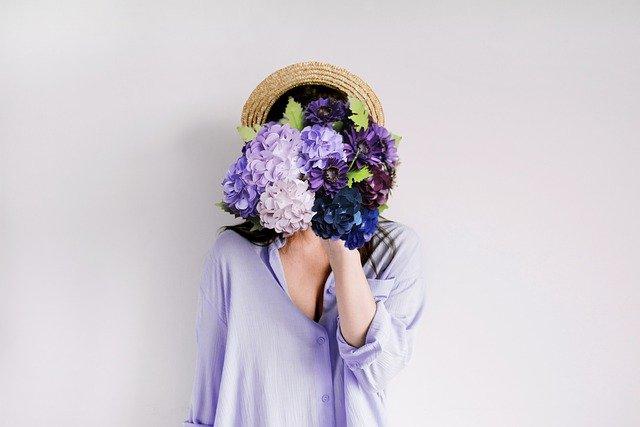 花束を顔の前で持つ女性の写真