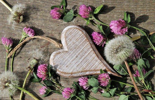 お花に囲まれた木製ハートプレートの写真